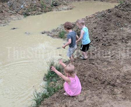 children playing in muddy creek