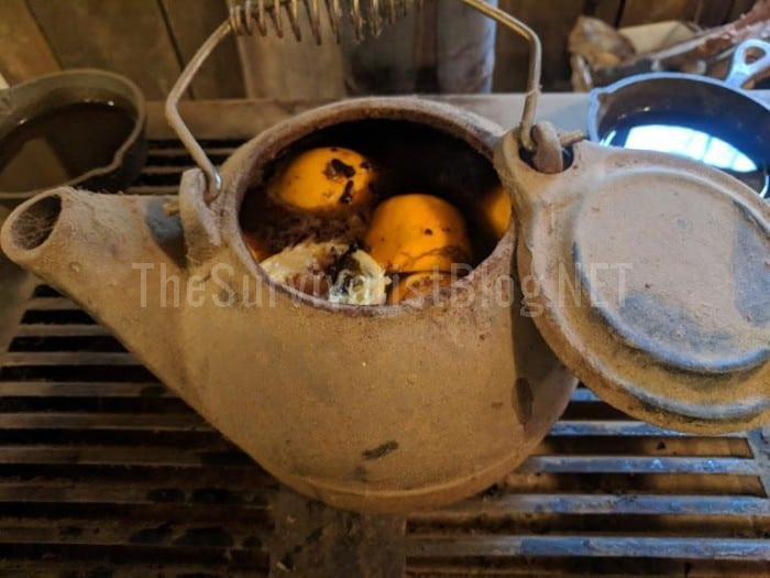 cast iron teapot filled with orange peels potpourri