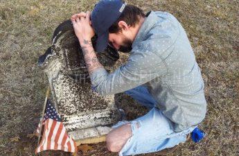 man kneeling next to tombstone