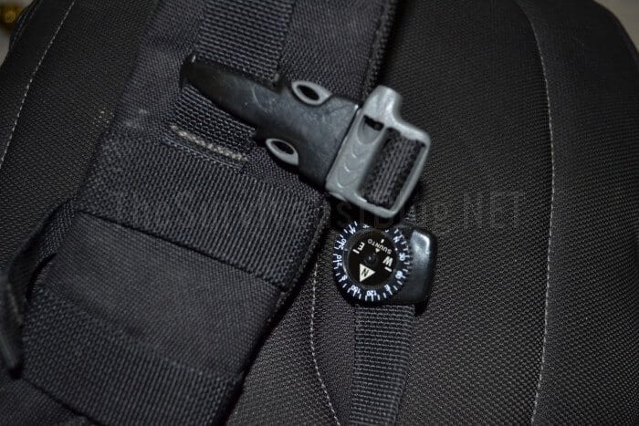 button compass attached to a backpack