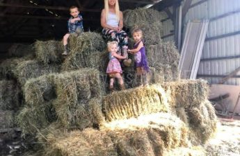 woman and kids on top of some bales of hay
