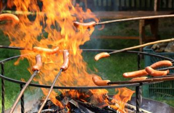 sausages on sticks on open flame